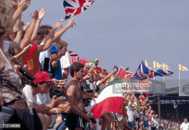 View of Formula One Grand Prix racing fans waving and cheering during the British Grand Prix at Silverstone England on 16th July 1989 Alain Prost...