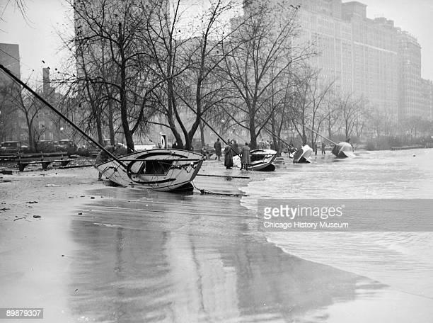 View of four boats lying on their sides on the shore of Lake Michigan at Belmont Harbor in Chicago Illinois after a storm 1929 People are standing...