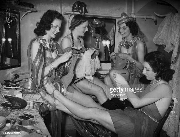 View of four chorus girls pictured knitting between acts in a dressing room backstage at the Windmill Theatre in London's West End as they help with...