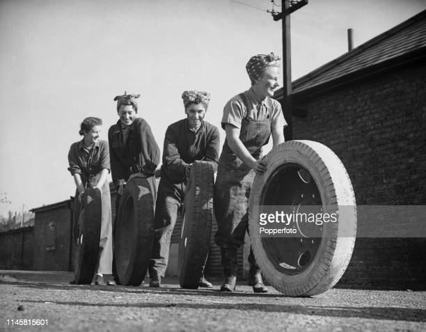 View of four headscarf wearing female members of the British Army's Auxiliary Territorial Service rolling lorry wheels across the barrack square...