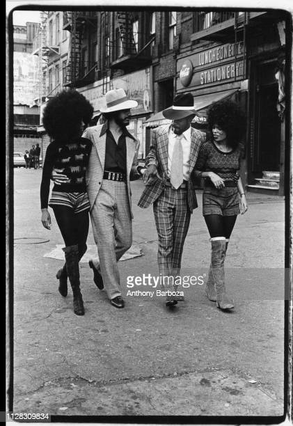 View of four people two men and two women as they walk along an unidentified street in Harlem New York New York 1971 The two women both wear their...