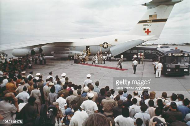 View of freed American prisoners of war walking along a red carpet from a USAF Lockheed C141 Starlifter aircraft to waiting ambulances at Clark Air...