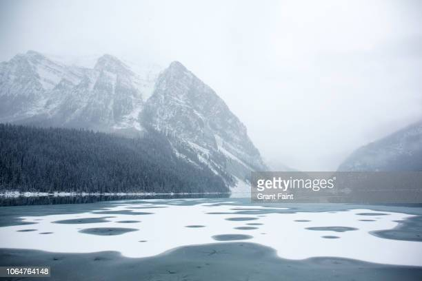 view of freezing lake during snowing. - image stock pictures, royalty-free photos & images