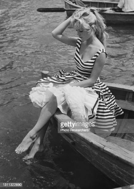 View of French actress Brigitte Bardot, in a striped dress, as she sits in the prow of a row boat and dips her feet in the water, 1950s.