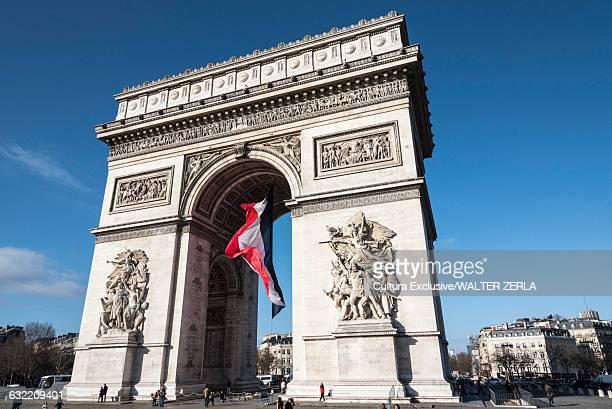 view of french flag and arc de triomphe, paris, france - arc de triomphe photos et images de collection