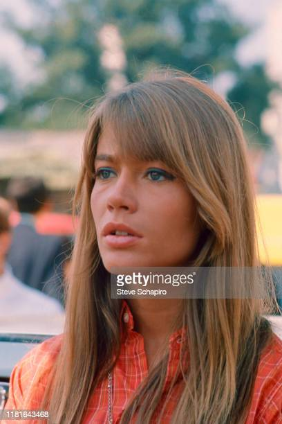 View of French singer and actress Francoise Hardy, in an orange, plaid shirt, as she poses outdoors, Venice, Italy, 1966.