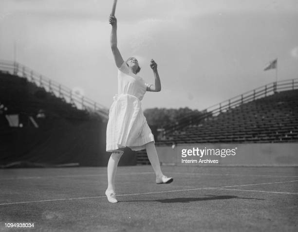 View of French tennis player Suzanne Lenglen as she jumps up to return an overhead volley, circa 1920.