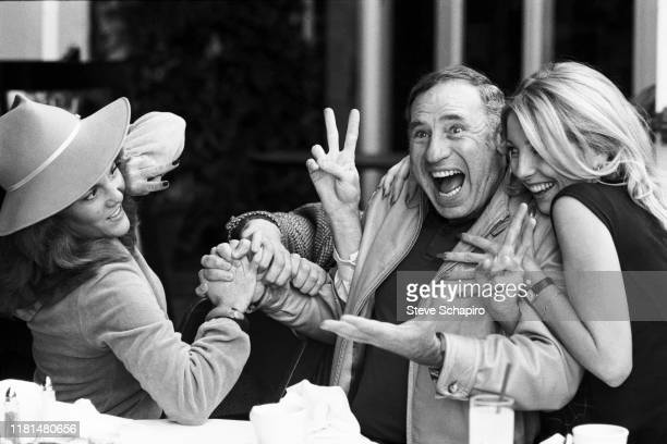 View of from left American actress Madeline Kahn director and actor Mel Brooks and actress Teri Garr at a restaurant as they clown around together...