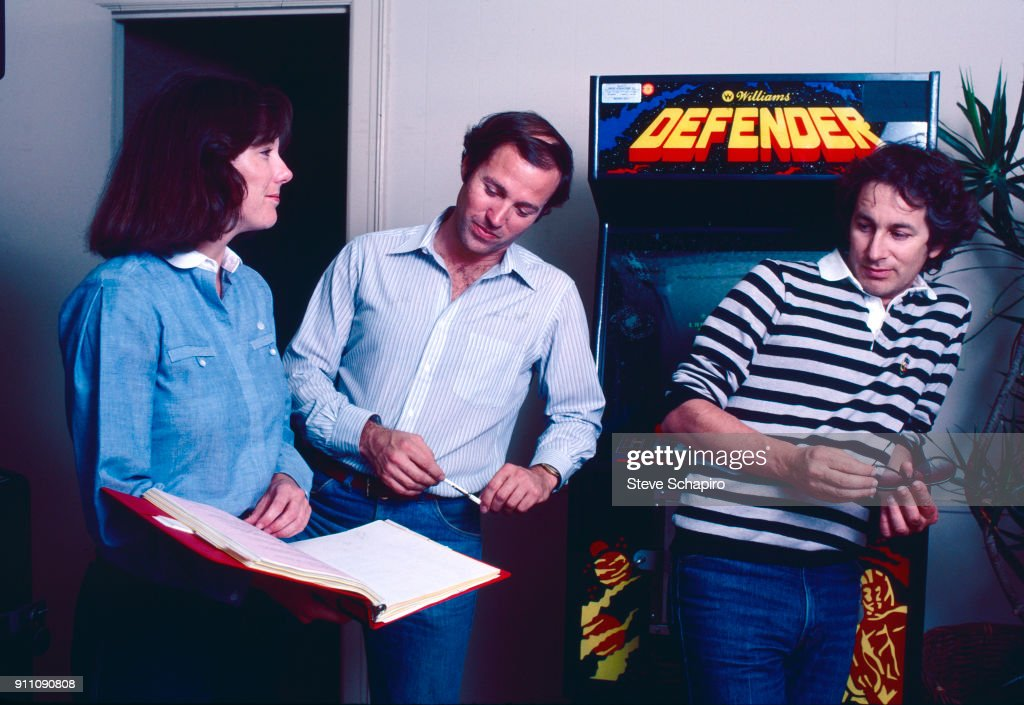 View of, from left, American film producers (and later married couple) Kathleen Kennedy and Frank Marshall, and film director Steven Spielberg, who leans on an Defender arcade game, Los Angeles, California, 1981.