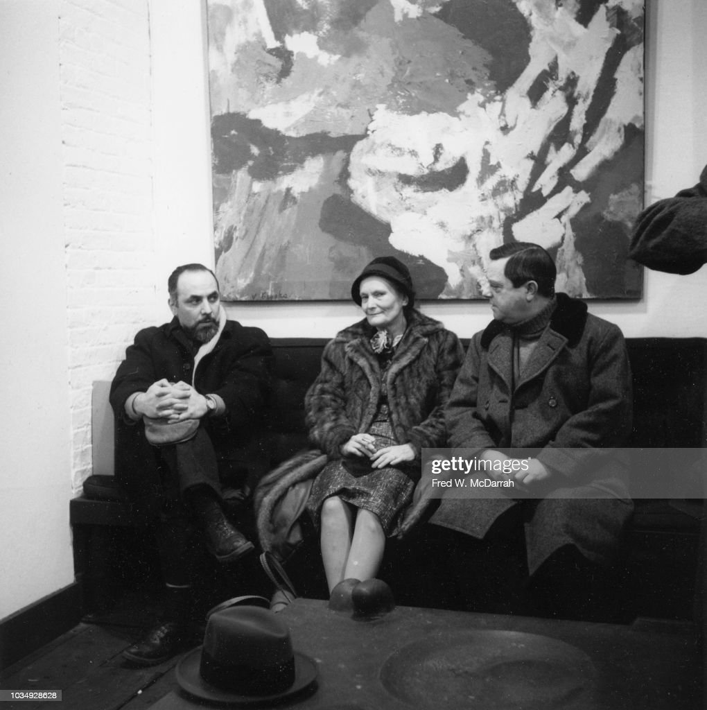 View of, from left, American painter Conrad Marca-Relli (born Corrado Marcarelli, 1913 - 2000), art collector and dealer Elinor 'Ellie' Poindexter (1906 - 1994), and artist Ludwig Sander (1906 - 1975) as they sit together on a couch at the Stable Gallery, New York, New York, February 2, 1959. They were attending the opening of an exhibition of works by James Brooks.