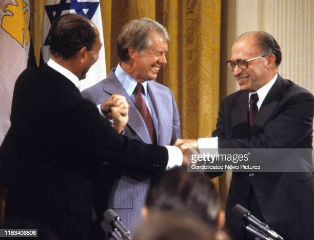 View of, from left, Egyptian President Anwar Al Sadat , US President Jimmy Carter , and Israeli Prime Minister Menachem Begin share a 3-way handshake...