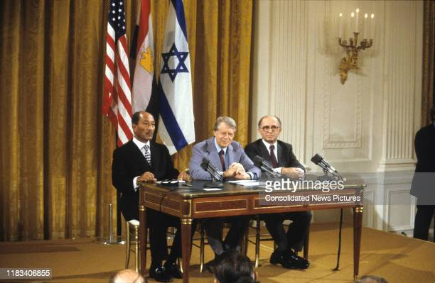 View of from left Egyptian President Anwar Al Sadat US President Jimmy Carter and Israeli Prime Minister Menachem Begin seated at a table during the...