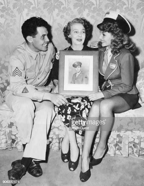 View of from left Sergeant Eduardo Cansino Jr his mother actress Volga Hayworth and sister actress Rita Hayworth as they sit together on a sofa...