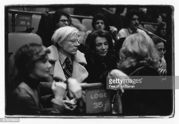 View of from second left American Pop artist Andy Warhol socialite Lee Radziwell and actress Sylvia Miles as they attend a concert at Madison Square...