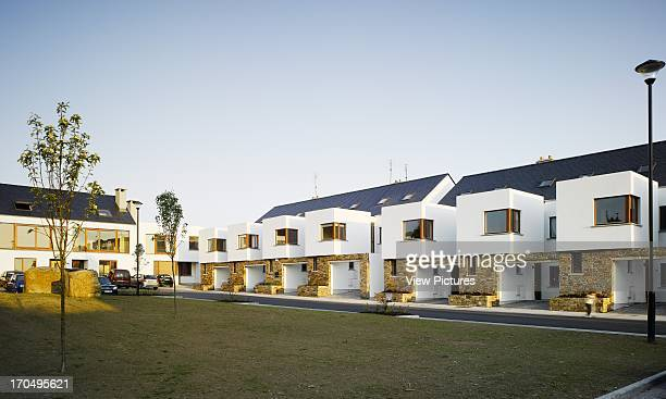 View of front facade of terraces from landscaped green space showing trees white render stone cladding and timber finishings with occupant Cluain...