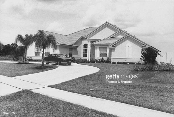 View of front yard and house of disgraced PTL minister Jim Bakker and his wife Tammy Faye w midsize sporty car in driveway