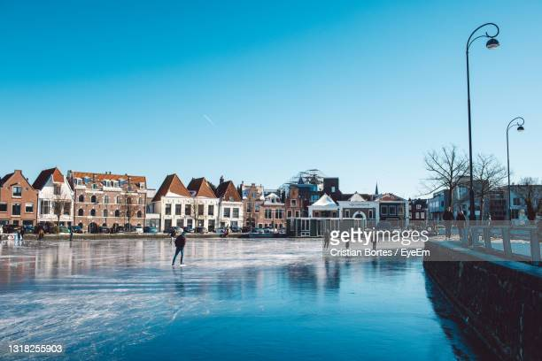 view of frozen river against buildings - bortes stock pictures, royalty-free photos & images