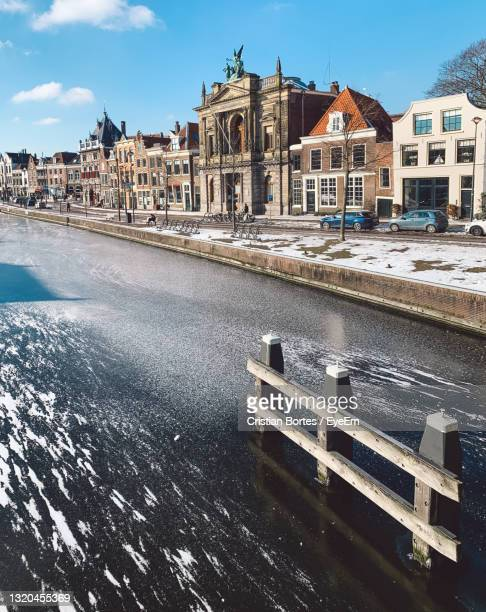 view of frozen river and buildings against cloudy sky - bortes stock pictures, royalty-free photos & images