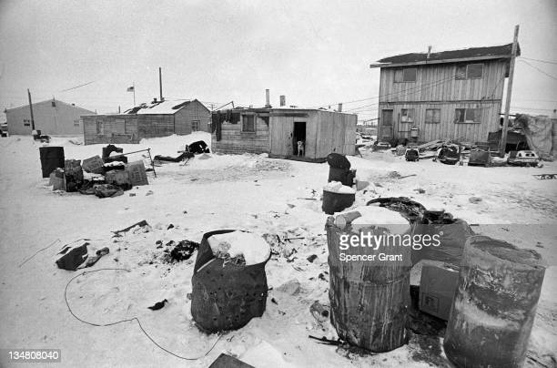 View of garbage frozen in latewinter snow along with Eskimo homes Barrow Alaska April 1973
