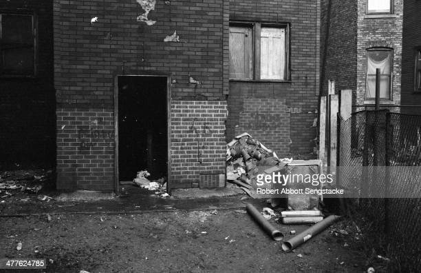 View of garbage strewn yard and boarded up windows in an apartment building in the Englewood neighborhood Chicago Illinois 1968