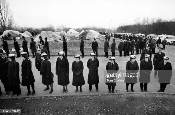View of genderseparated line of police officers as they surround a tent city of antinuclear campaigners at the RAF Greenham Common air base Berkshire...