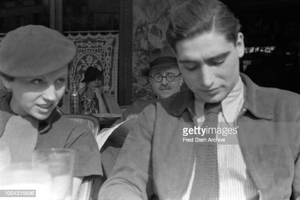 View of German photographer Gerda Taro and Hungarian photographer Robert Capa as they sit togather at a sidewalk cafe Paris France 1936 Other...