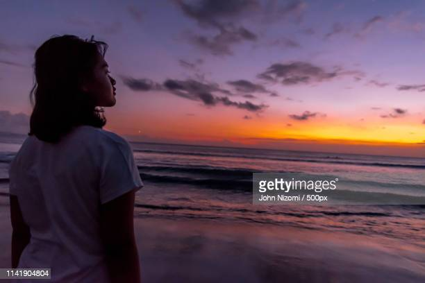 view of girl at sunset - moody sky stock pictures, royalty-free photos & images