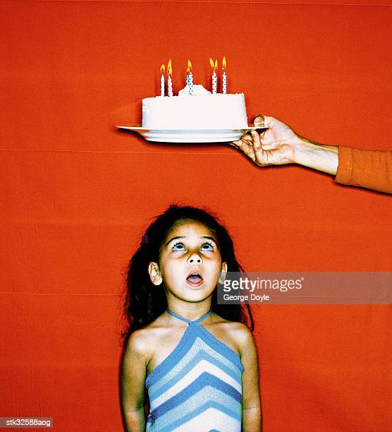 view of girl (6-8) looking up at a birthday cake held above her head
