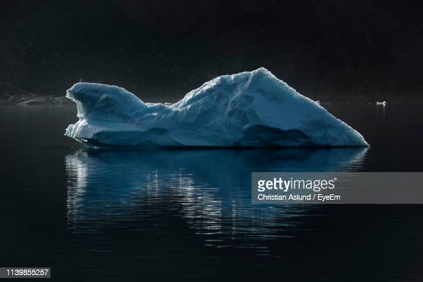 view of glacier in lake against sky at night - berg photos et images de collection