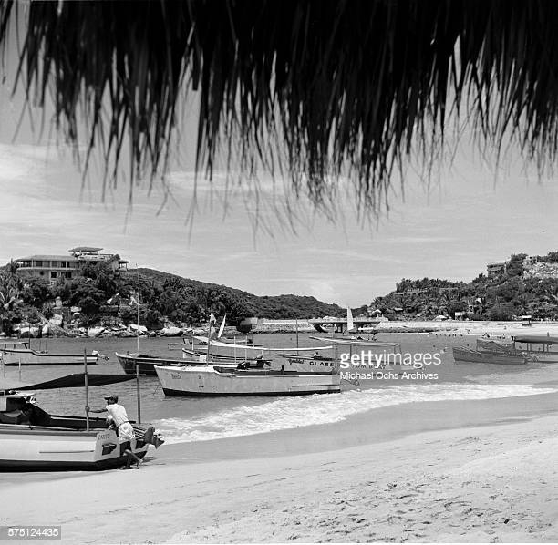 A view of glass bottom boats off the sandy beach in Acapulco Mexico