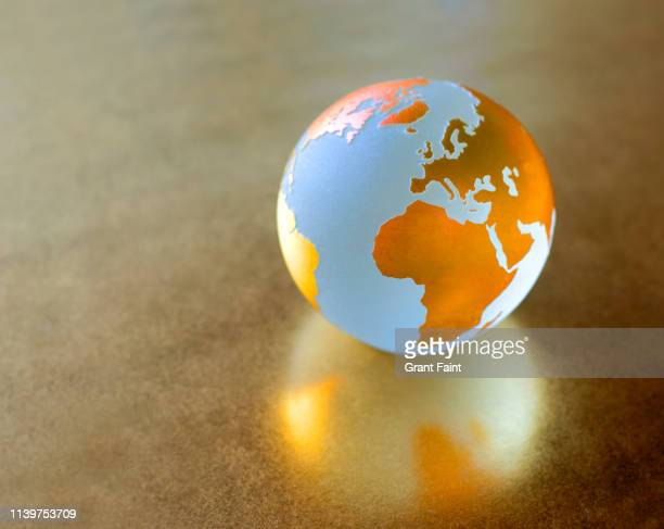 view of globe on gold background. - global village stock pictures, royalty-free photos & images