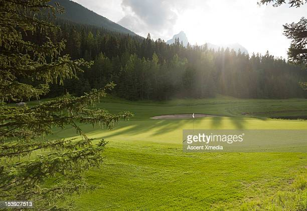 view of golf course green at sunrise, mountains - green golf course stock pictures, royalty-free photos & images