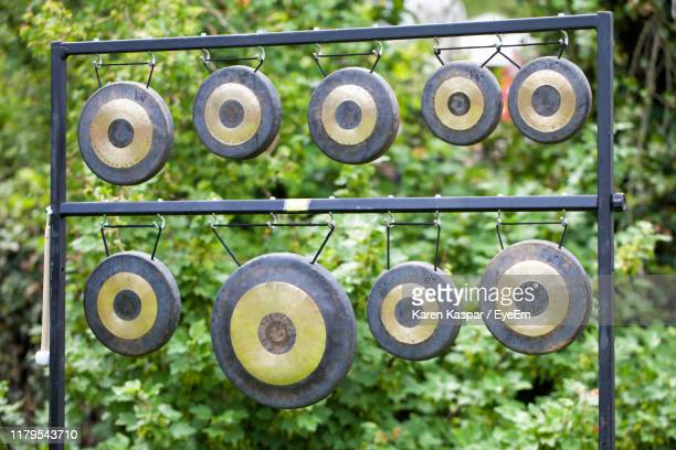 view of gongs against plants - gong stock pictures, royalty-free photos & images