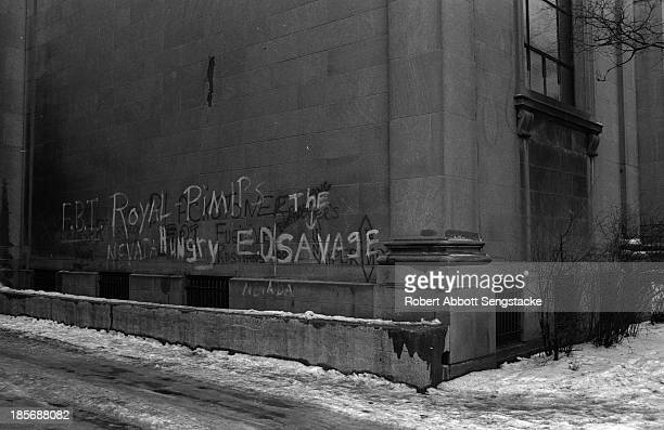 View of graffiti written on the wall of an building beside an ice-covered sidewalk, Chicago, Illinois, 1960s. The graffiti reads, in part,...