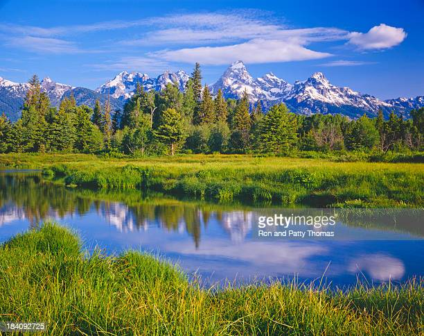 view of grand teton national park from across a river - jackson hole stock pictures, royalty-free photos & images