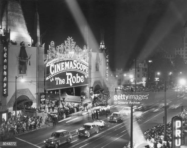View of Grauman's Chinese Theater in Hollywood with floodlights shining and crowd standing in line at the premiere of director Henry Koster's film,...