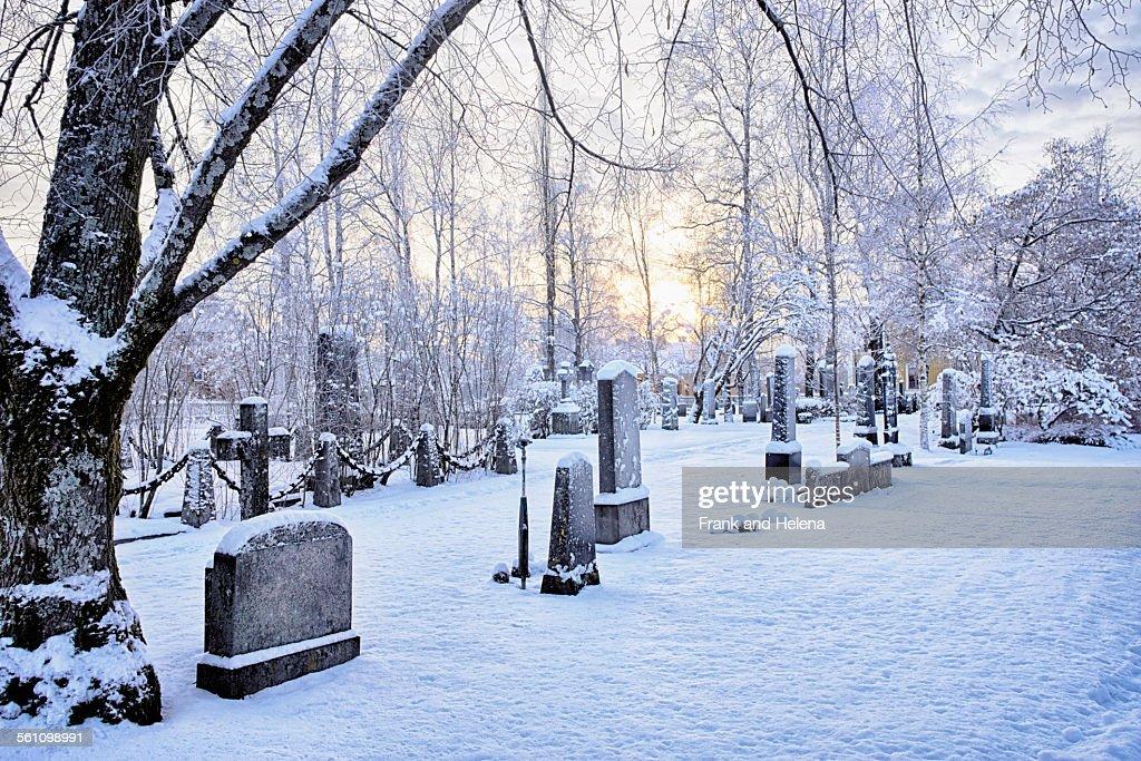 View of grave stones in snow covered cemetery at dusk, Hemavan, Sweden : Stock Photo
