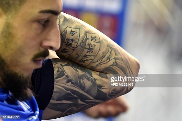 View of Greece's forward Kostas Mitroglou's tatoos taken during a press conference in Aracaju on June 21 three days before a group C match against...