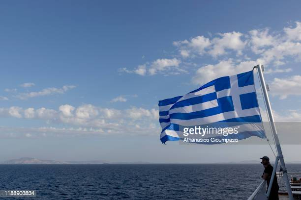 View of greek flag from ship leaving the port Tino island on November 08, 2019 in Tinos, Greece.