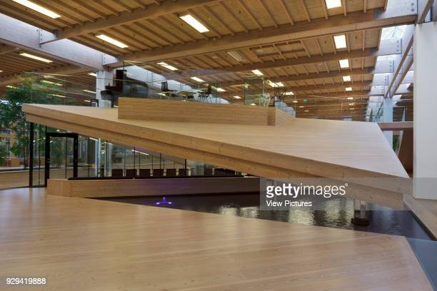 View of ground floor with sloping Douglas fir timber platform and reflecting pool in foreground IBC Innovation Factory Kolding Denmark Architect...