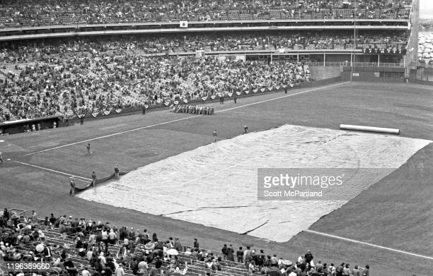 View of groundskeepers as they cover the field during a 35-minute rain delay before on opening day baseball game at Shea Stadium, in the Corona...