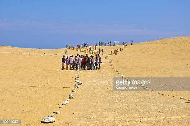 View of groups of tourists visiting the desert and Supay Beach Supay means devil in the Quechua language and it was named like this because of the...