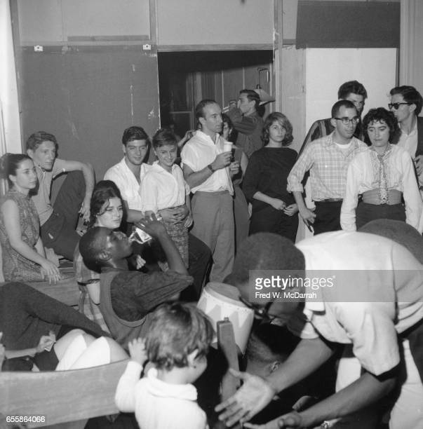 View of guests at a birthday party for Beat artist Ted Joans New York New York July 25 1959 Among the crowd at center a bongo player pauses to drink...