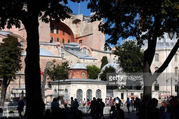 view of hagia sophia between silhouettes of tres, at sultanahmet square, istanbul turkey - três pessoas stock pictures, royalty-free photos & images