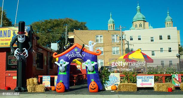 View of Halloween decorations including inflatable figures and haybales outside Fatso's Last Stand hot dog restaurant in the Ukrainian Village...