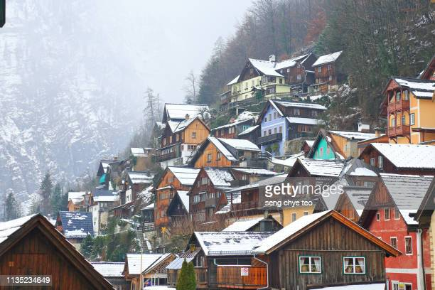 view of hallstatt townscape and mountains against winter sky - hallstatt stock pictures, royalty-free photos & images