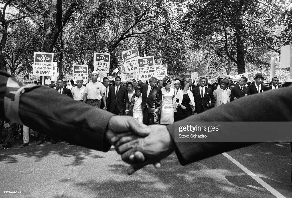 View, across hands held together, the front line of demonstrators during the March on Washington for Jobs and Freedom, Washington DC, August 28, 1963. Among those visible are, left from center, 11-year-old David Robinson (center) and his parents, American baseball player Jackie Robinson (1919 - 1972) and Rachel Robinson, and Civil Rights activists Rosa Parks (1913 - 2005) and Reverend Fred Shuttlesworth (1922 - 2011). The march and rally provided the setting for the Reverend Martin Luther King Jr's iconic 'I Have a Dream' speech.