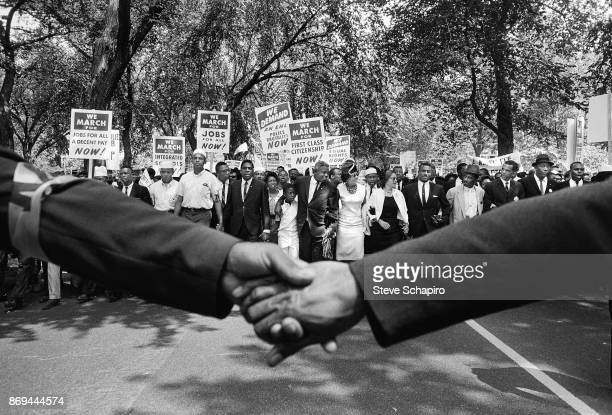 View of hands held together, and the front line of demonstrators during the March on Washington for Jobs and Freedom, Washington DC, August 28, 1963....