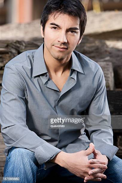 3/4 view of handsome hispanic young man sitting outdoors - handsome mexican men stock pictures, royalty-free photos & images