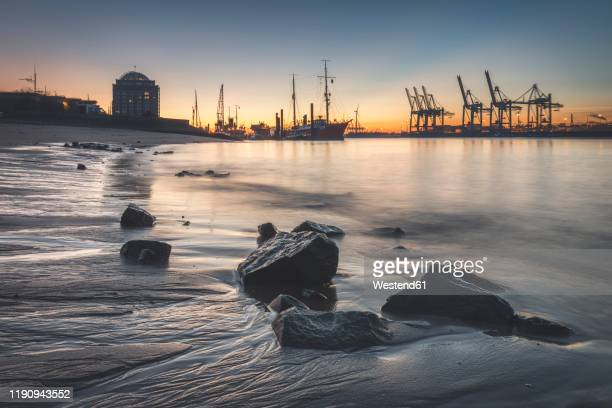 view of harbor against sky during sunset at hamburg, germany - amburgo foto e immagini stock